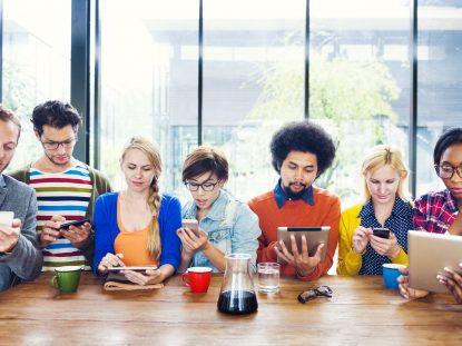 Photographie d'un groupe de six personnes assises à table et tenant des smartphones