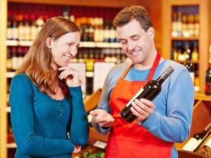 Photographie d'un sommelier qui conseille une bouteille de vin à une cliente